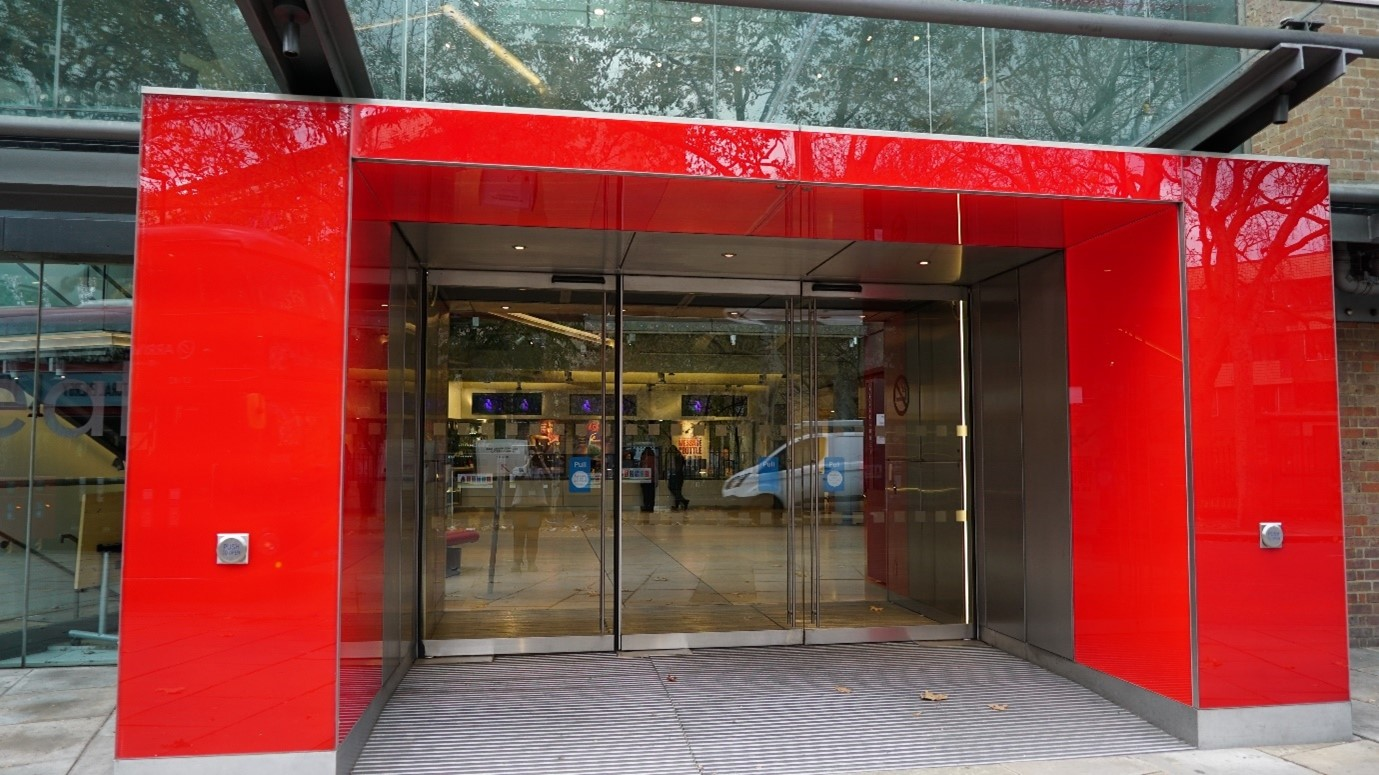 The red front entrance doorway of Sadler's Wells Theatre with glass doors