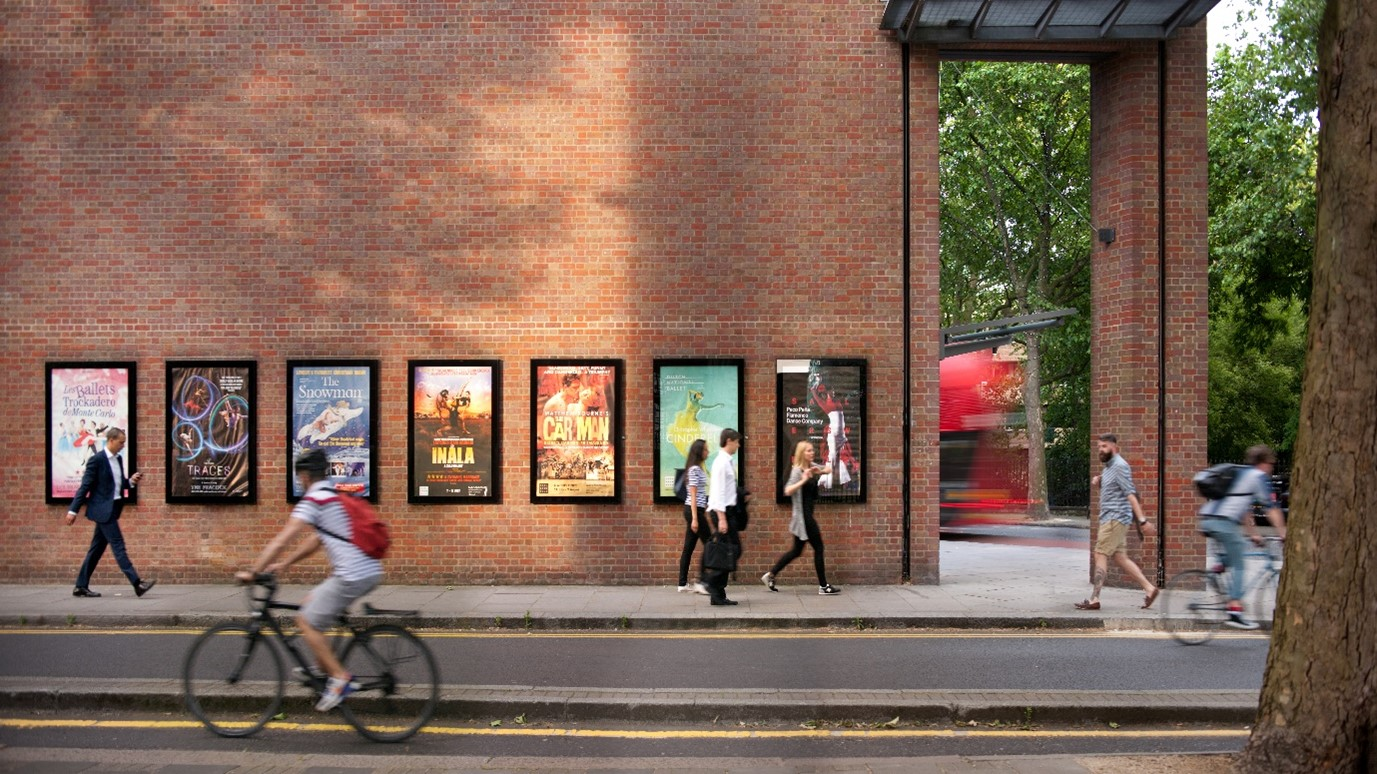 A photo of the outside wall of Sadler's Wells Theatre building with show posters and pedestrians and a cyclist passing by